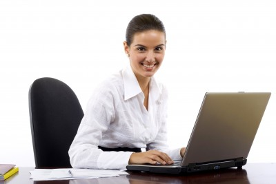 Smiling woman typing on a laptop